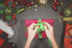 Young woman decorating a box for Christmas gift Stock Image