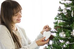 Decorating christmas tree. Young woman decorating christmas tree Stock Photo