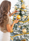 Young woman decorating christmas tree with christmas ball Royalty Free Stock Photo
