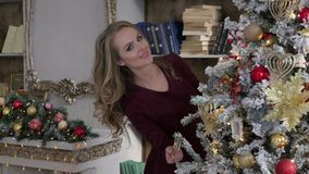 Young woman decorating a Christmas tree at home. Young woman decorating a Christmas tree stock video