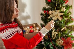 Young woman decorating Christmas tree at home, wearing winter sweater. Preparing to New year. Young woman decorating Christmas tree with toys at home, wearing royalty free stock images
