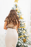 Young woman decorating christmas tree. rear view Royalty Free Stock Photos