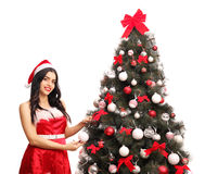 Young woman decorating a Christmas tree. Young woman in Santa costume decorating a Christmas tree and looking at the camera isolated on white background Stock Photo