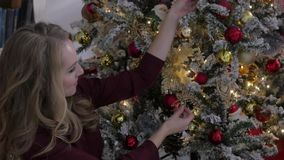 Young woman decorating a Christmas tree at home. Young woman decorating a Christmas tree stock footage