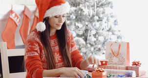 Young woman decorating her Christmas gifts Royalty Free Stock Photography