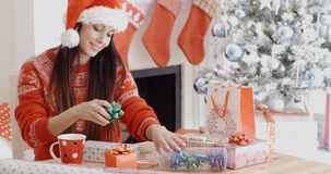 Young woman decorating her Christmas gifts Stock Photos