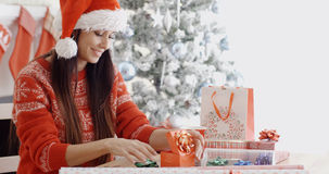 Young woman decorating her Christmas gifts Royalty Free Stock Images