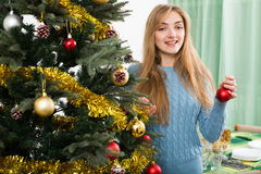 Young woman decorating Xmas tree and smiling at home Stock Photo