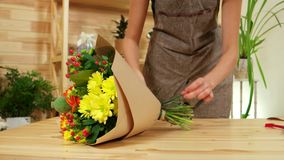 Young woman decorator wraps the flowers in the wrapping paper, happy girl at work in a flower shop stock video