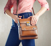 Young woman in deep blue jeans holding a bag Stock Photography