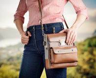Young woman in deep blue jeans holding a bag Royalty Free Stock Photos