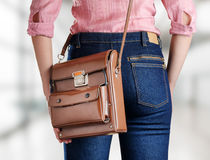 Young woman in deep blue jeans holding a bag Royalty Free Stock Image