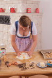 Young woman with deep cleavage kneads dough. Royalty Free Stock Image