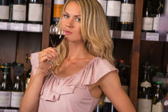 Young woman degustating red wine. Young woman in a supermarket degustating red wine Royalty Free Stock Photography