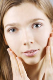 Young woman delightfully touching her face Stock Images