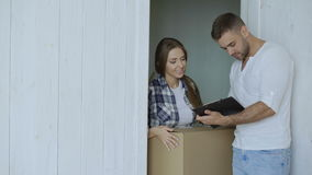 Young woman deliver cardboard box to customer at home. Man sign in clipboard for receiving parcel