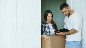 Young woman deliver cardboard box to customer at home. Man sign in clipboard for receiving parcel Stock Photos