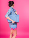 Young woman in denim holding blue handbag Stock Photo