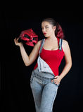 A young woman in denim overalls and red biking helmet Royalty Free Stock Images