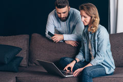Young woman in denim shirt,sitting at home on couch and using laptop.Guy holding smartphone. Stock Image