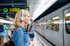 Young woman in denim shirt at the underground platform, waiting. Beautiful young blond woman in denim shirt with earphones, standing at the underground platform Stock Images