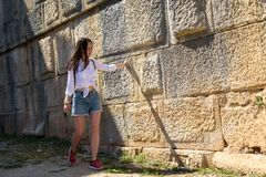 A young woman in denim shorts and a backpack walks through the ruins of the amphitheater, a touch of history, travel, move up, cop. Young woman in denim shorts stock image