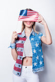 Young woman in denim vest with stars and stripes hiding face by small american flag Stock Image