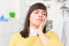 Young woman at the dentist with a tooth pain. Feeling uncomfortable Royalty Free Stock Photography