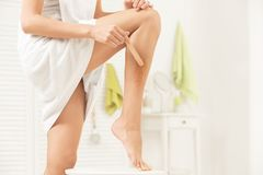 Young woman depilating her leg with liquid sugar. At home royalty free stock photography
