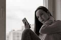 A young woman is depressed on a windowsill near the window of the house, close-up, black and white. stock photos