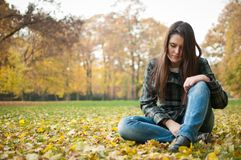 Young woman in depression outdoor. Portrait of young worried person siting in depression outdoor in fallen leaves Stock Photo