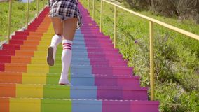 Young woman descending rainbow colored steps stock video