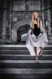Young Woman Descending Steps of Castle. Beautiful young woman descending steps of castle Stock Image
