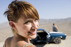 Young woman in desert by car and friends, smiling, portrait, close-up Royalty Free Stock Photos