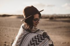 Young woman in the desert on a windy day with glasses and hat royalty free stock photo