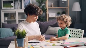 Young woman teaching her little son to make paper collage at table at home. Young woman designer is teaching her little son to make paper collage sitting at stock video footage