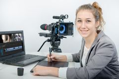 Young woman designer using graphics tablet for video editing stock images