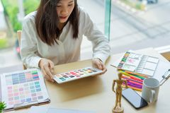 Young woman designer working with color samples for selection on office desk stock photo
