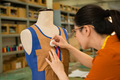 Young woman designer working hard with dummy. Beautiful young woman designer working hard with dummy model and drawing markings on clothes sample confirm new royalty free stock photo