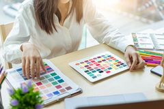 Young woman designer working with tablet color samples for selection on office desk stock image