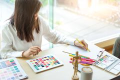 Young woman designer working with tablet color samples for selection on office desk royalty free stock photo