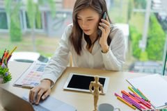 Young woman designer working with tablet color samples for selection on office desk, royalty free stock photo