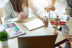 Young woman designer working with tablet color samples for selection on office desk stock photo