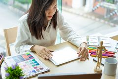 Young woman designer working with tablet color samples for selection on office desk royalty free stock photos