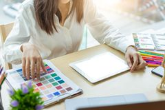 Young woman designer working with tablet color samples for selection on office desk royalty free stock photography
