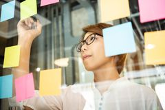 Young woman designer writing new ideas at sticky notes. On glass wall. Brainstorming concept stock photo