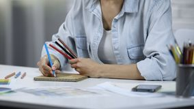 Young woman designing interior, freelancer doing work, coloring with pencils. Stock photo royalty free stock image