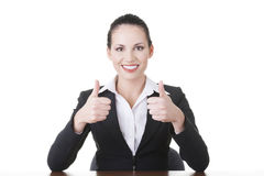 Young woman at the desk gesturing OK Stock Images