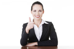 Young woman at the desk gesturing OK Royalty Free Stock Image