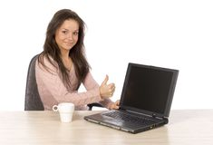 Young woman at the desk with laptop showing OK Royalty Free Stock Images